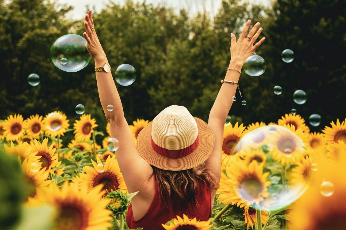 photography of woman surrounded by sunflowers